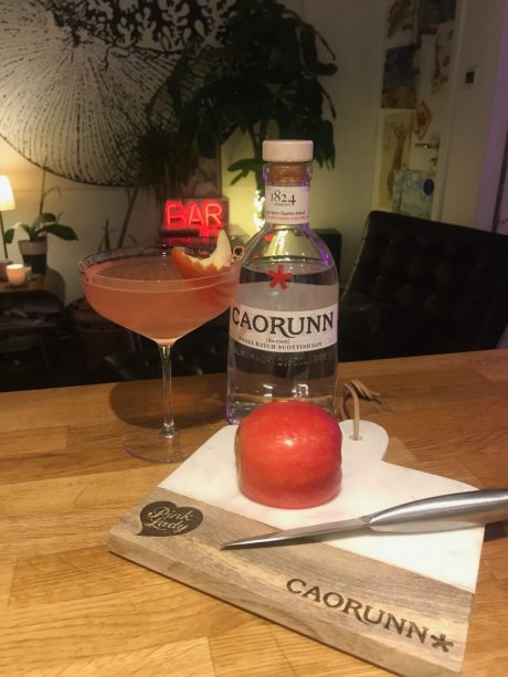 A pink cocktail drink next to a bottle of Caorunn gin.